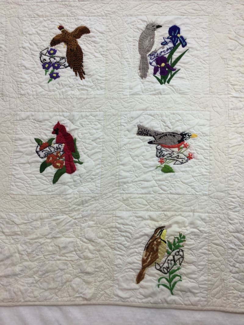 Image of an unfinished quilt featuring state birds and flowers that I completed for a customer